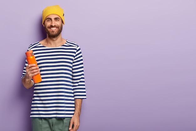 Studio shot van knappe lachende hipster man met donkere haren, draagt gele hoed en casual gestreepte trui, houdt kolf warme drank, geniet van vrije tijd, geïsoleerd over paarse muur, vrije ruimte aan de rechterkant