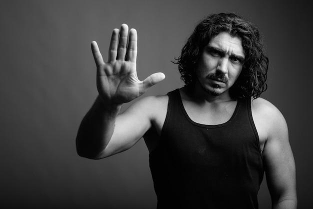 Studio shot van knappe macho man met krullend haar en snor tegen een grijze achtergrond in zwart-wit black