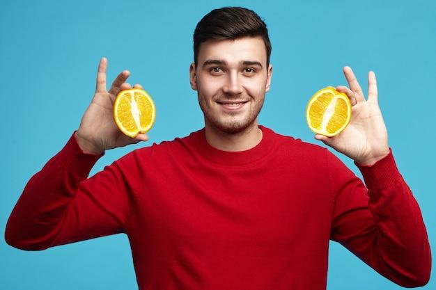 Studio shot van knappe positieve jonge europese mannelijke vegetariër in rode trui poseren bij blauwe muur