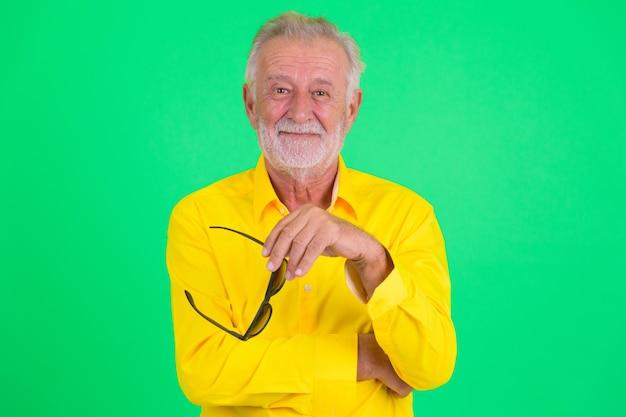Studio shot van knappe senior bebaarde zakenman tegen een groene achtergrond