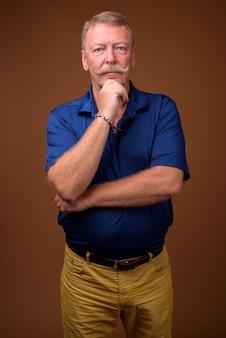 Studio shot van knappe senior man met snor blauw poloshirt dragen tegen bruin