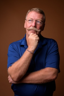 Studio shot van knappe senior man met snor dragen blauwe polo shirt en bril tegen bruin