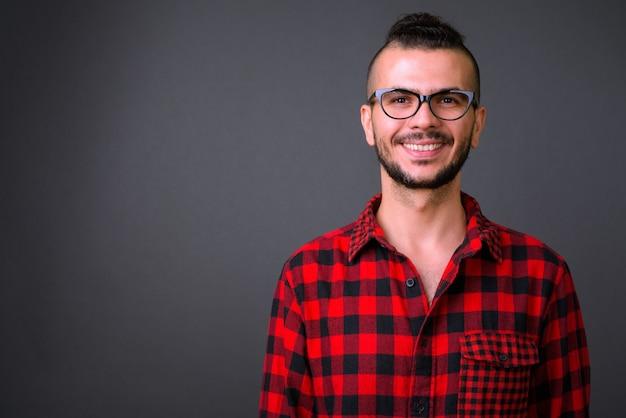 Studio shot van knappe turkse man met bril tegen een grijze achtergrond