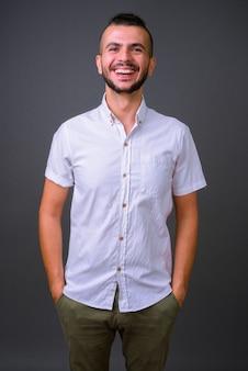 Studio shot van knappe turkse man tegen een grijze achtergrond