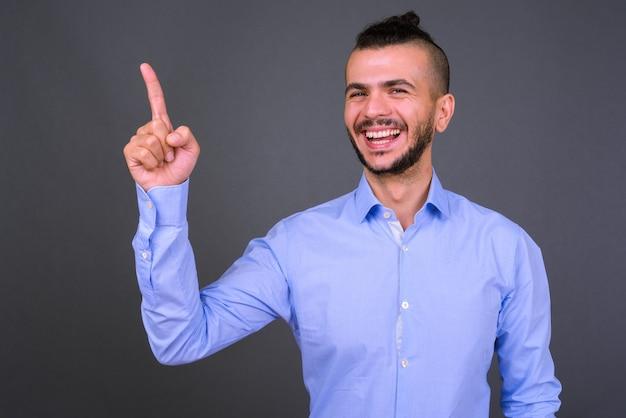 Studio shot van knappe turkse zakenman tegen een grijze achtergrond