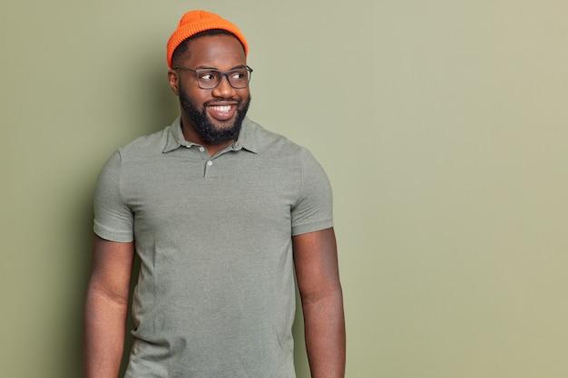 Studio shot van knappe volwassen man kijkt opzij naar promotietekst heeft vrolijke uitdrukking dikke baard witte tanden gekleed in vrijetijdskleding