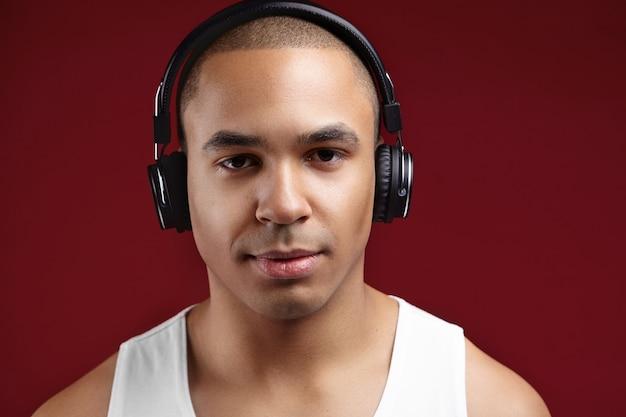 Studio shot van lachende zelfverzekerde jonge afro-amerikaanse gladgeschoren man genieten van nieuw album van zijn favoriete artiest via stijlvolle koptelefoon, met behulp van online muziektoepassing op een elektronisch apparaat