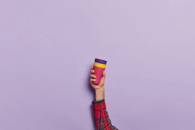 Studio shot van mannenhand houdt koffiemok met warme drank