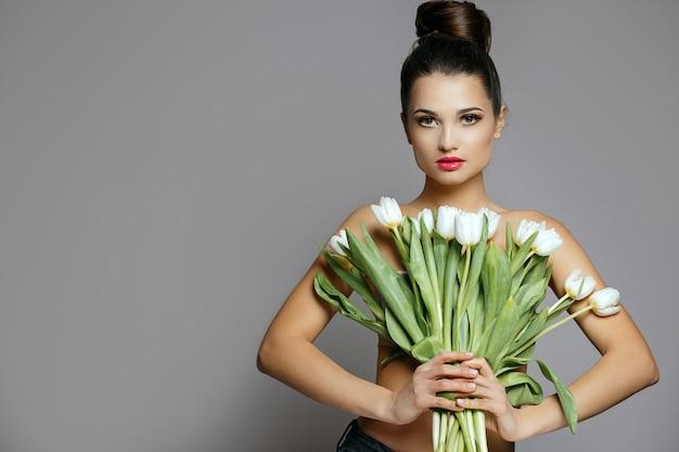 Studio shot van modieuze jonge vrouw met een boeket van een witte tulpen. studio opname over een grijze achtergrond. lege ruimte