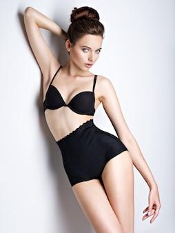 Studio shot van mooi en sexy meisje met bruin haar zwarte lingerie dragen