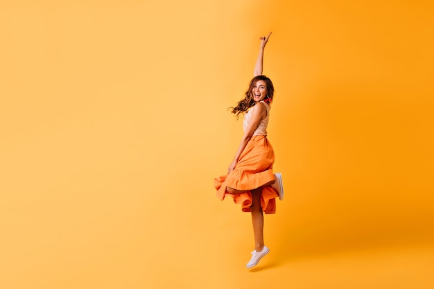 Studio shot van mooi meisje in oranje rok en witte schoenen. opgewonden roodharige dame die op geel springt.