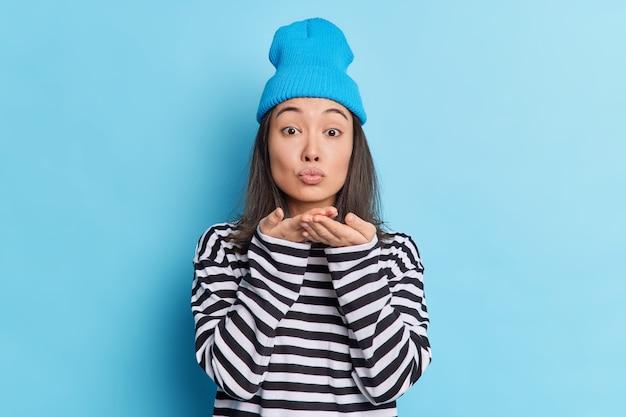 Studio shot van mooie aziatische vrouw blaast airkiss houdt lippen gevouwen handpalmen in de buurt van mond drukt liefde uit voor vriendje