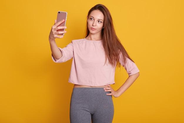 Studio shot van mooie bruinharige vrouw met steil haar in grijze broek en roze shirt nemen selfie