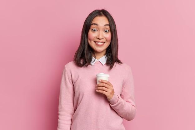 Studio shot van mooie brunette aziatisch meisje heeft koffiepauze zachtjes glimlacht naar camera toont witte tanden gekleed in casual jumper poses in studio