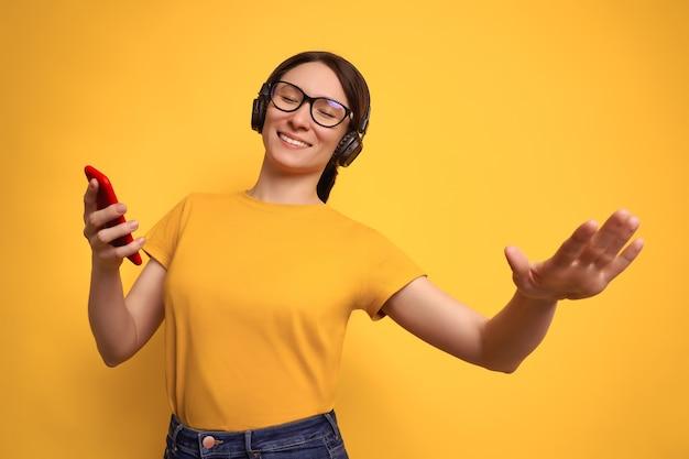 Studio shot van mooie brunette vrouw in geel t-shirt en draadloze koptelefoon luistert naar luide muziek en dansen op geel