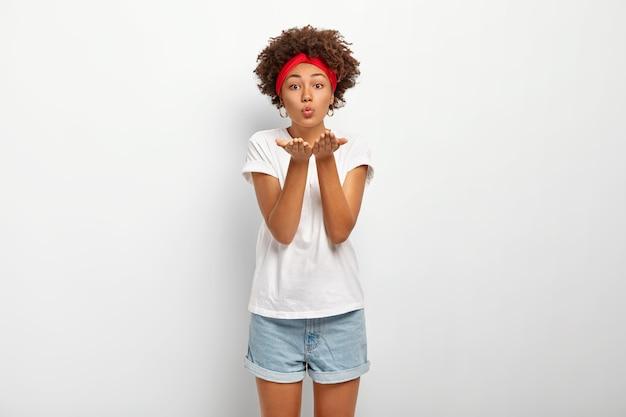 Studio shot van mooie dame met afro haar, stuurt luchtkus naar geliefde, drukt liefde en genegenheid uit, is in een speelse bui
