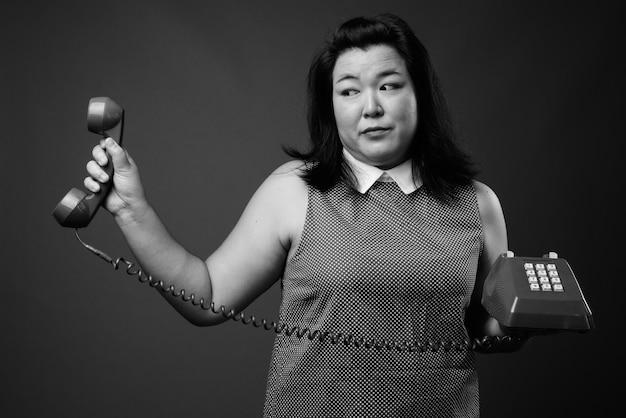 Studio shot van mooie dikke aziatische vrouw, gekleed in jurk tegen een grijze achtergrond in zwart en wit