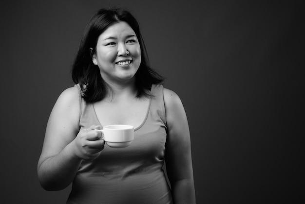 Studio shot van mooie dikke aziatische vrouw, gekleed in mouwloze jurk tegen een grijze achtergrond in zwart en wit