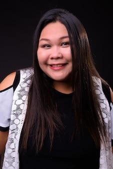 Studio shot van mooie dikke aziatische vrouw tegen zwarte achtergrond