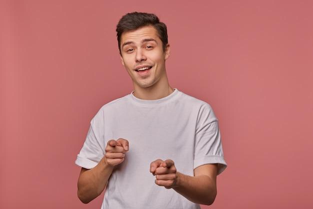 Studio shot van mooie donkerharige jonge man hand opsteken en met wijsvingers vooruit wijzen, staande over roze achtergrond in vrijetijdskleding, zelfverzekerd naar camera kijken en glimlachen