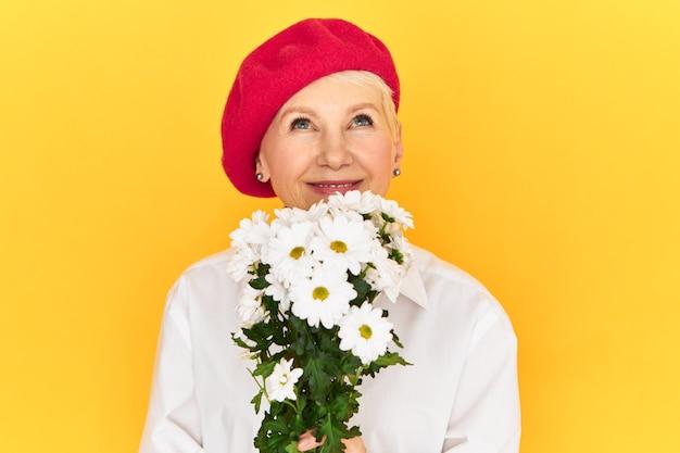Studio shot van mooie elegante franse vrouw gepensioneerde m / v in stijlvolle rode baret genieten van aroma van witte madeliefjes, opzoeken met een blije glimlach.