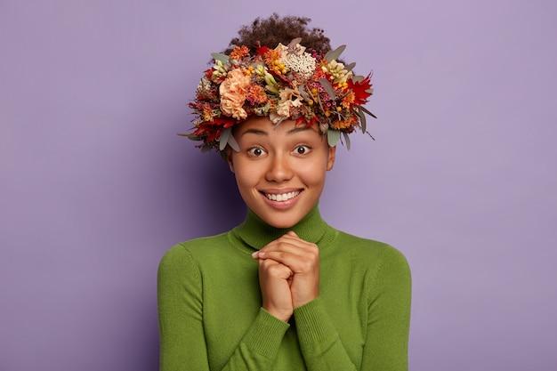 Studio shot van mooie jonge dame glimlacht gelukkig, houdt de handen tegen elkaar gedrukt, kijkt hopelijk naar de camera, draagt herfst handgemaakte krans, casual poloneck, modellen tegen paarse achtergrond
