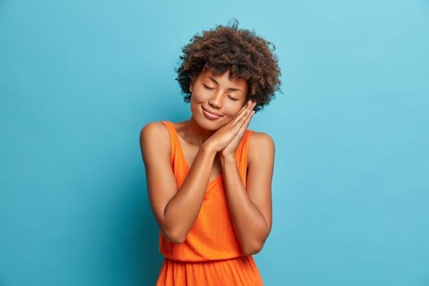 Studio shot van mooie jonge vrouw leunt op geperste handpalmen sluit de ogen en heeft een aangename glimlach dromen over iets gekleed in een oranje zomerjurk geïsoleerd op blauwe studiomuur