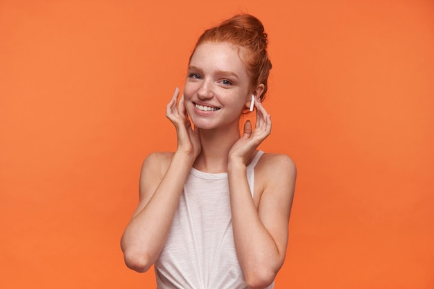 Studio shot van mooie jonge vrouw met foxy broodje kapsel camera kijken met positieve en charmante glimlach, luisteren naar muziek met koptelefoon terwijl staande over oranje achtergrond