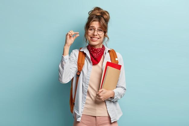 Studio shot van mooie studente toont weinig gebaar, zegt dat ze niet veel nodig heeft, houdt blocnote vast