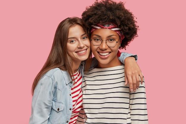 Studio shot van mooie twee jonge gelukkig gemengd ras vrouwen staan dicht bij elkaar