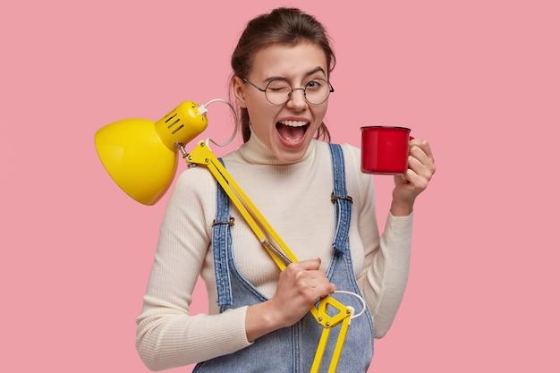 Studio shot van mooie vrolijke vrouw knippert oog, heeft plezier met vrienden na het doen van hometaak, maakt gebruik van tafellamp, drinkt hete thee of koffie