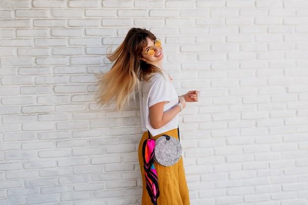 Studio shot van onbezorgde vrouw in heldere zomer outfit poseren over witte bakstenen muur