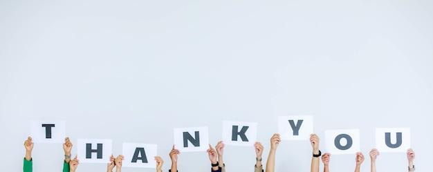 Studio shot van onherkenbare niet-geïdentificeerde groep stafofficier in hoofdkantoor met dank u alfabet kartonnen papieren bord boven het hoofd met waardering voor de klant op witte achtergrond.