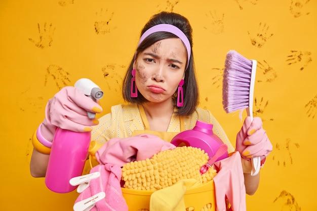 Studio shot van ontevreden aziatische vrouw houdt borstel en wasmiddel kijkt met vermoeide uitdrukking op camera poses in de buurt van wasmand doet huishoudelijk werk geïsoleerd over gele muur