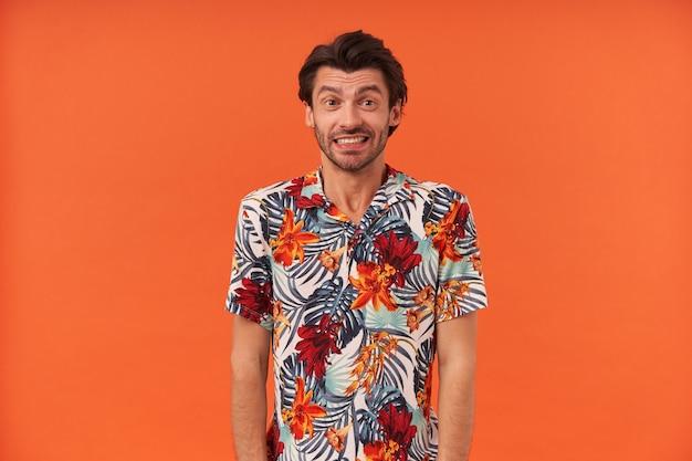 Studio shot van onzeker beschaamde jonge man met stoppels in kleurrijk shirt voelt zich verward en kijkt naar de camera