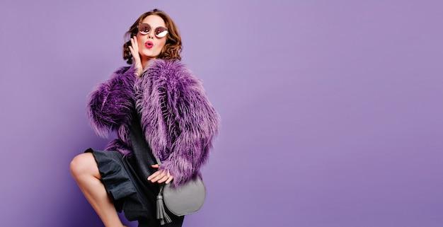 Studio shot van op blote voeten leuke vrouw met trendy grijze tas poseren met plezier
