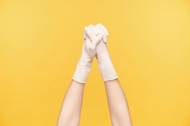 Studio shot van opgeheven jonge vrouw dient rubberen handschoenen in die samen vouwen en vingers gekruist houden terwijl ze geïsoleerd zijn over oranje achtergrond