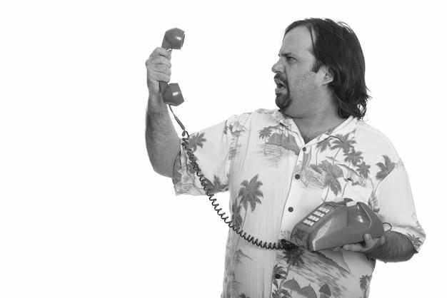 Studio shot van overgewicht bebaarde toeristische man klaar voor vakantie geïsoleerd tegen een witte achtergrond in zwart-wit