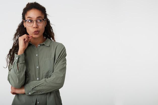 Studio shot van peinzende bruinharige krullende dame met donkere huid haar mond draaien terwijl ze bedachtzaam opzij kijkt, staande op een witte achtergrond in vrijetijdskleding