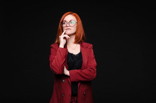 Studio shot van peinzende elegante vrouw in rode jas en zwarte kanten top in brillen. roodharige vrouw in bril en pak die nadenkend wegkijkt met de vinger naar haar gezicht. isoleer op zwart.