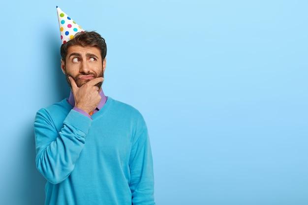Studio shot van peinzende man met verjaardag hoed poseren in blauwe trui