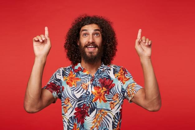 Studio shot van positieve jonge brunette gekrulde man met baard opdagen met wijsvingers terwijl poseren tegen rode achtergrond in veelkleurig gebloemd overhemd