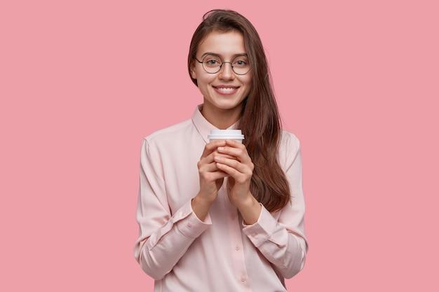 Studio shot van positieve schoolmeisje grijpt koffie om productief te werken, houdt papieren kopje drank, bezoekt café, draagt formeel overhemd