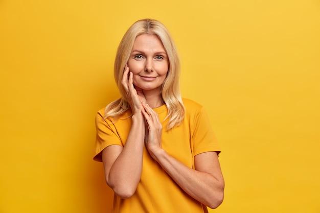 Studio shot van rustige mooie vrouw met een gezonde huid raakt gezicht zachtjes draagt minimale make-up heeft tedere glimlach zorgt voor haar teint draagt gele t-shirt in één toon met achtergrond.