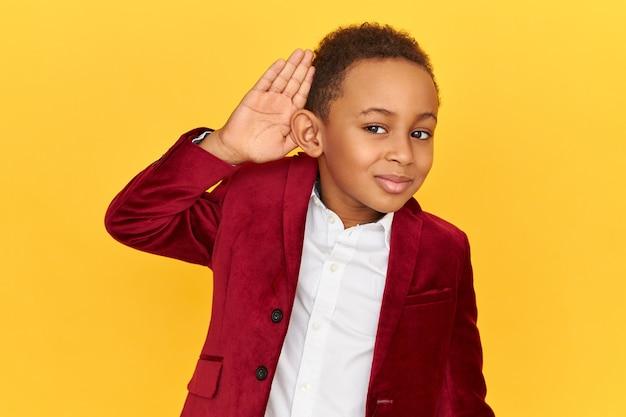 Studio shot van schattige snoopy donkere huid kleine jongen met een nieuwsgierige blik, met de handpalm tegen zijn oor om duidelijker te horen terwijl hij privégesprekken afluistert.