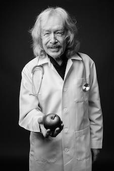 Studio shot van senior man arts met snor tegen grijze muur