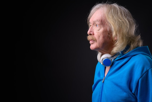 Studio shot van senior man met snor blauwe jas dragen tegen een grijze achtergrond