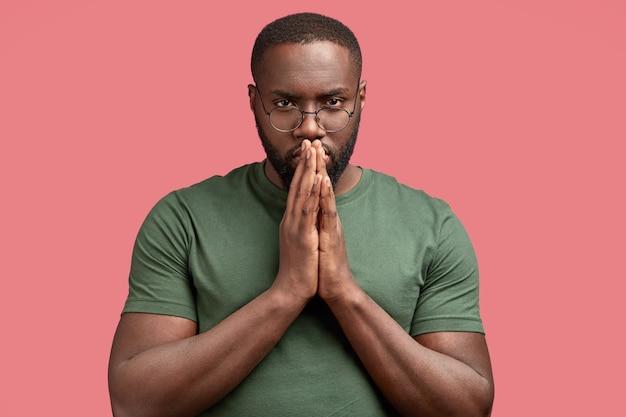 Studio shot van serieuze man houdt handen in gebed gebaar, aanbidt voor iets