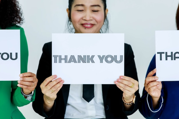 Studio shot van stripe letters dank u papier teken houden door lachende vrouwelijke officier in pak op borst waardering met anonieme collega's tonen aan klanten op witte achtergrond.
