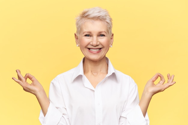 Studio shot van succesvolle rijpe zakenvrouw draagt een wit formeel overhemd breed glimlachend, mudra gebaar maken, mediteren in haar kantoor, vol energie, poseren tegen gele achtergrond